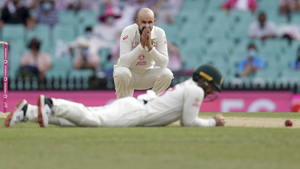 Australia's Nathan Lyon reacts as teammate Australia's Matthew Wade missed a catch opportunity during play on day two of the third cricket test between India and Australia at the Sydney Cricket Ground, Sydney, Australia, Friday, Jan. 8, 2021. (AP Photo/Rick Rycroft)