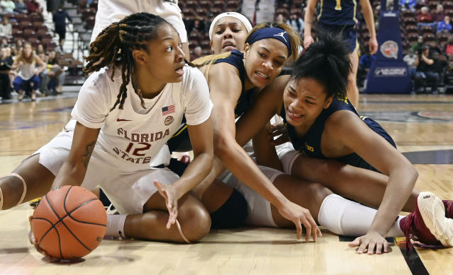 Michigan's Kayla Robbins, center, and Naz Hillmon, right, pressure Florida State's Nicki Ekhomu, left, as they reach over Florida State's Kiah Gillespie, back, in the first half of an NCAA college basketball game, Sunday, Dec. 22, 2019, in Uncasville, Conn. (AP Photo/Jessica Hill)