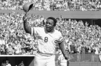 FILE - In this Saturday, Oct. 16, 1976, file photo, Cincinnati second baseman Joe Morgan tips his helmet to the fans as he rounds the bases after a homer in the first inning against the New York Yankees at Riverfront Stadium in Cincinnati. The affection drenches Clint Hurdle's voice when he talks of them, when he appraises the list of those recently gone — childhood idols who became teammates and opponents, teammates and opponents who became acquaintances, acquaintances who became friends.(AP Photo/File)