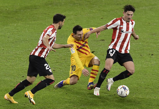 Barcelona's Lionel Messi center, is tackled during the Spanish La Liga soccer match between Athletic Bilbao and Barcelona at San Mames stadium in Bilbao, Spain, Wednesday, Jan. 6, 2021.(AP Photo/Alvaro Barrientos)