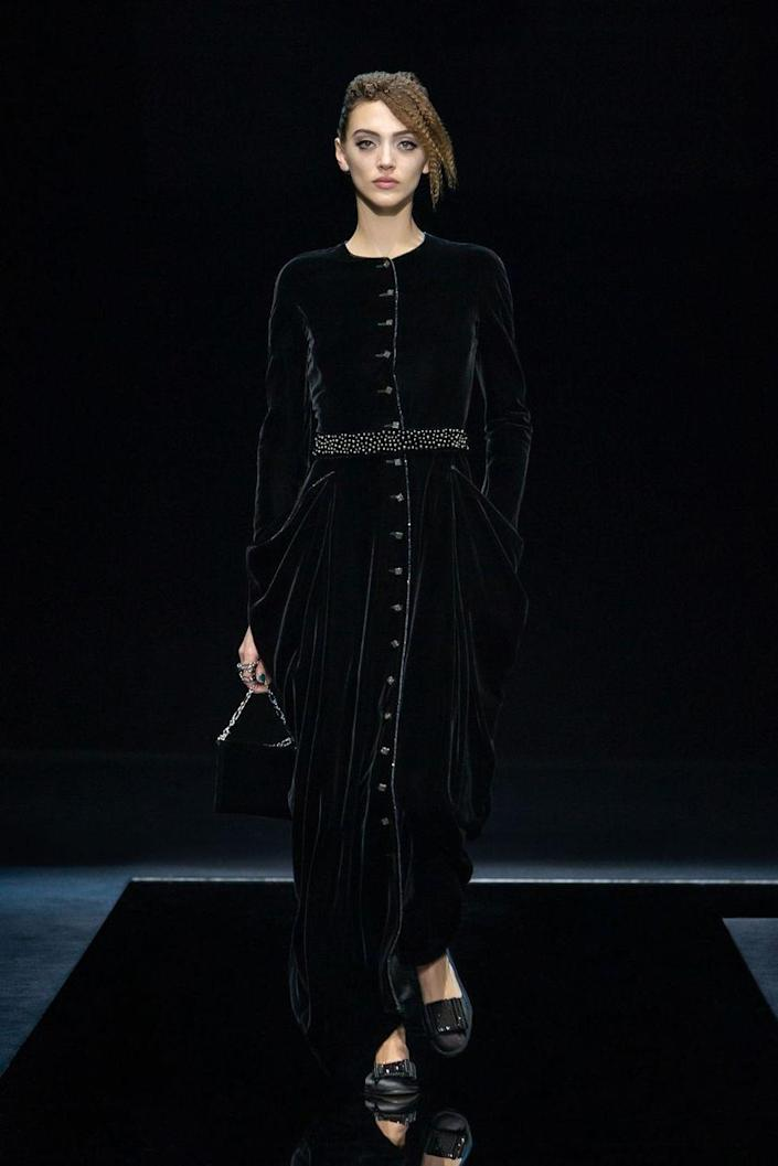 "<p>Giorgio Armani is forever soft and subtle—precise, but never harsh. His particular presentation of femininity is brought to life with ruffles and petals and peeks of skin (jackets that flare open over the navel and long skirts layered over shorter ones to let legs emerge mid-stride). Rich velvets and rippling silks coyly suggest you touch without demanding it, a demure attitude upheld even by the more must-touch crystals and spiral ruffles. Entitled ""Nocturnal,"" it seems fair to read the collection's palette as a sign that we're collectively emerging from what's felt like one very long night. Every hue of blue was used, including the inkiest iteration of a midnight sky, and spots of blush warmed things up much like the first tentacles of sun do upon the dawning of a new day. Lovely and surefooted, it's a wonderful forecast for the future.<em>—Leah Melby Clinton</em></p>"