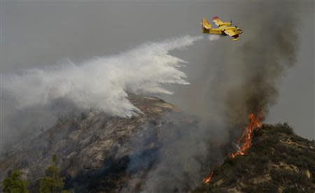 "A ""super scooper"" air tanker makes waters drops as firefighters battle a fast-moving California wildfire, so-called the ""Colby Fire"", in the hills of Glendora January 16, 2014. REUTERS/Gene Blevins"
