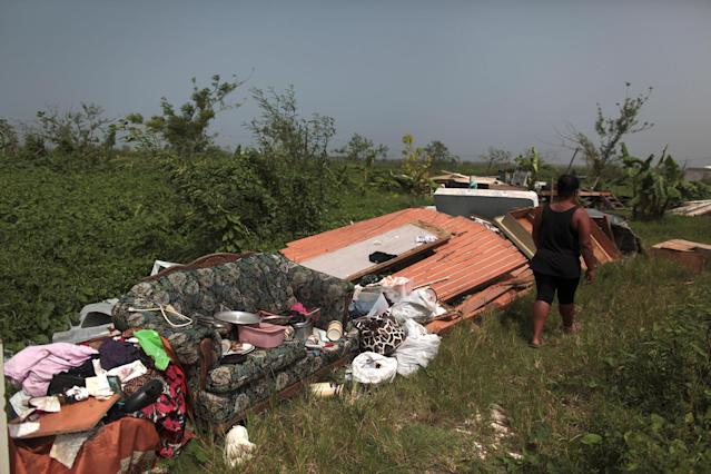 <p>Cynthia Calderon walks past some furniture and other belongings she could salvage, after the island was hit by Hurricane Maria in September, in Toa Alta, Puerto Rico, Oct. 19, 2017. (Photo: Alvin Baez/Reuters) </p>