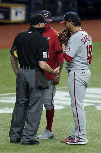 Washington Nationals starting pitcher Anibal Sanchez (19) and manager Dave Martinez talk to home plate umpire Dan Iassogna (58) after Sanchez was taken out of the game against the Tampa Bay Rays during the fifth inning of a baseball game Tuesday, Sept. 15, 2020, in St. Petersburg, Fla. (AP Photo/Chris O'Meara)
