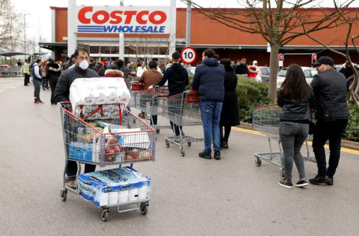 A masked customer leaves with shopping as other customers queue to enter a Costco Wholesalers in Chingford, Britain