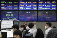 A currency trader talks with his colleague at the foreign exchange dealing room of the KEB Hana Bank headquarters in Seoul, South Korea, Thursday, March 4, 2021. Asian shares fell Thursday, tracking a decline on Wall Street as another rise in bond yields rattled investors who worry that higher inflation may prompt central banks to raise ultra-low interest rates. (AP Photo/Ahn Young-joon)