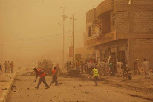 Enveloped by a sand storm, Iraqis clear the debris following two car bombs in the western city of Ramadi