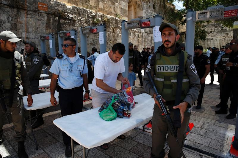 A Palestinian man empties his bag as he walks through a recently installed metal detector outside the Lion's Gate, a main entrance to Al-Aqsa mosque compound (AFP Photo/AHMAD GHARABLI)