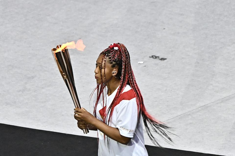 <p>Japan's tennis player Naomi Osaka carries the Olympic torch in the Olympic Stadium during the opening ceremony of the Tokyo 2020 Olympic Games, in Tokyo, on July 23, 2021. (Photo by Jeff PACHOUD / AFP) (Photo by JEFF PACHOUD/AFP via Getty Images)</p>