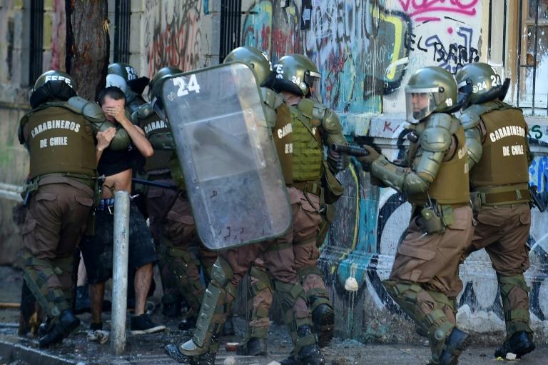 Riot policemen arrest a demonstrator during a protest against the government in Santiago on November 16, 2019