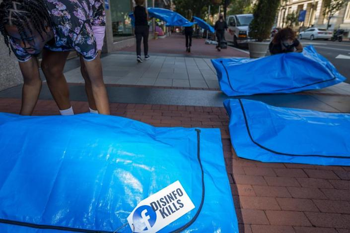 """At Facebook's Washington DC headquarters, activists lay body bags that read """"disinfo kills""""."""