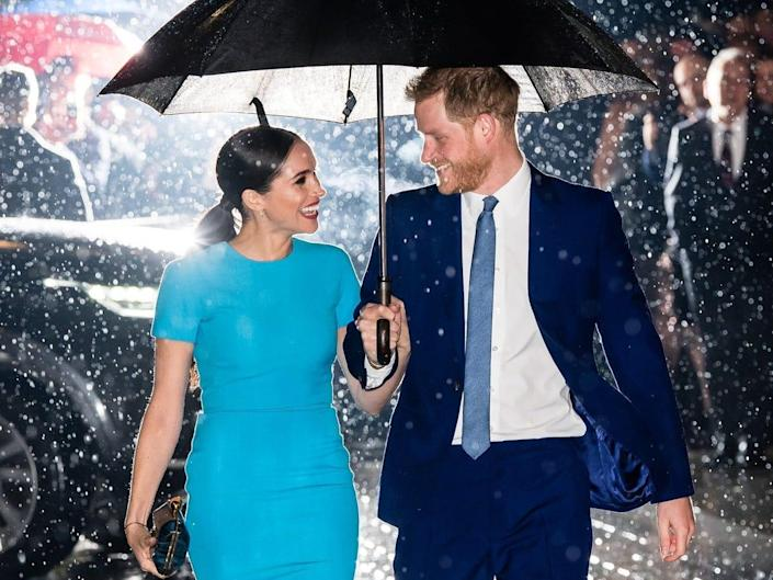 Prince Harry and Meghan Markle share an umbrella and smile at each other in March 2020.