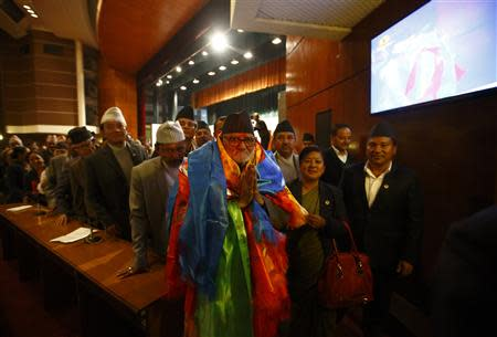 Newly elected Nepalese Prime Minister Sushil Koirala greets media personnel as he walks out from the Parliament after being elected as the Prime Minister in Kathmandu