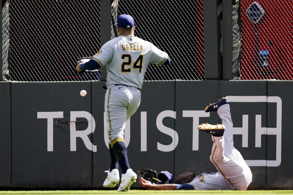 Milwaukee Brewers center fielder Lorenzo Cain (6) loses the ball after colliding with the fence on a hit by Atlanta Braves' Adam Duvall during the fourth inning of Game 3 of a baseball National League Division Series, Monday, Oct. 11, 2021, in Atlanta. (AP Photo/John Bazemore)