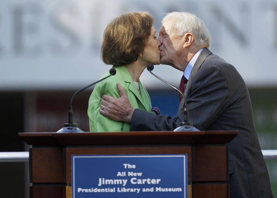 FILE - This Oct. 1, 2009 file photo shows former President Jimmy Carter getting a kiss from his wife Rosalynn as she introduces him during a reopening ceremony for the newly redesigned Carter Presidential Library in Atlanta. Jimmy Carter and his wife Rosalynn celebrate their 75th anniversary this week on Thursday, July 7, 2021. (AP Photo/John Bazemore, File)