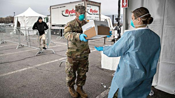 PHOTO: A National Guard soldier handles COVID-19 swab tests at a drive-thru testing center at Lehman College, on March 28, 2020, in the Bronx, New York City. The center, opened March 23, can test up to 500 people per day for the coronavirus. (John Moore/Getty Images)