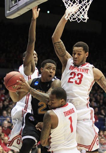 Iona guard Lamont Jones (2) is defended by Ohio State forward Sam Thompson, center Amir Williams (23), and forward Deshaun Thomas (1) in the first half of a second-round game at the NCAA college basketball tournament, Friday, March 22, 2013, in Dayton, Ohio. (AP Photo/Skip Peterson)
