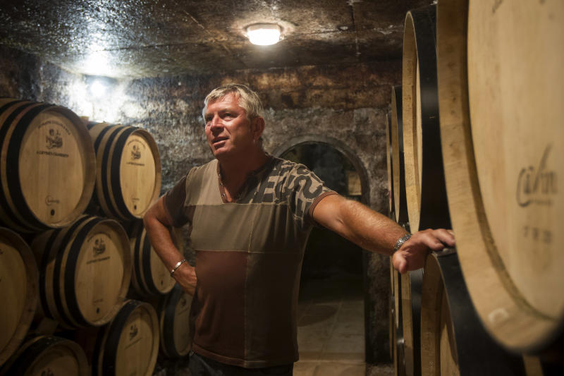 """In this Sept. 10, 2012 photo, Jean-Michel Guillon, owner of the Domaine Guillon, stands in his cellar Gevrey-Chambertin in Burgundy, Eastern France in Burgundy, Eastern France. Guillon, who led a local bid to buy the thousand-year-old Chateau de Gevrey-Chambertin, says a state agency valued the estate at 3.5 million euros. His group first offered 4 million euros, then 5 million, but the Masson family, which has owned the estate for more than 150 years, refused. """"They said, 'We want more, we want a million each,'"""" Guillon says. (AP Photo/Laurent Cipriani)"""