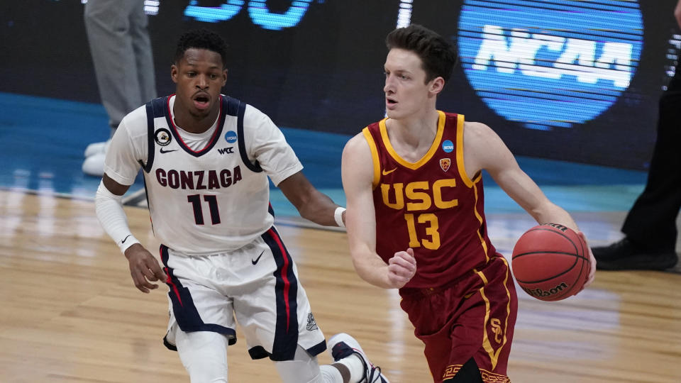 Southern California guard Drew Peterson (13) drives past Gonzaga guard Joel Ayayi (11) during the first half of an Elite 8 game in the NCAA men's college basketball tournament at Lucas Oil Stadium, Tuesday, March 30, 2021, in Indianapolis. (AP Photo/Michael Conroy)