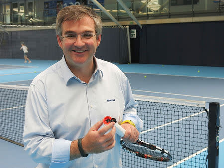 Eric Babolat, CEO and Chairman of Babolat poses for a photograph holding a hi-tech, 'connected' tennis racquet in Roehampton