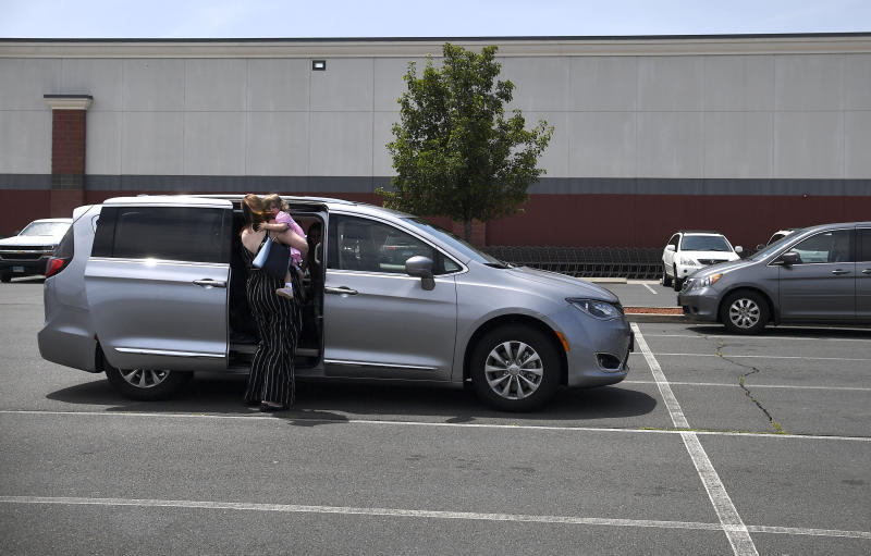 In this Tuesday, July 16, 2019, Melanie Matcheson picks up daughter Caroline out the car seat inside her Chrysler Pacifica in a shopping area parking lot in Southington, Conn. Melanie bought an eight-passenger silver Pacifica in mid-June for about $31,000, getting an $8,000 discount. (AP Photo/Jessica Hill)