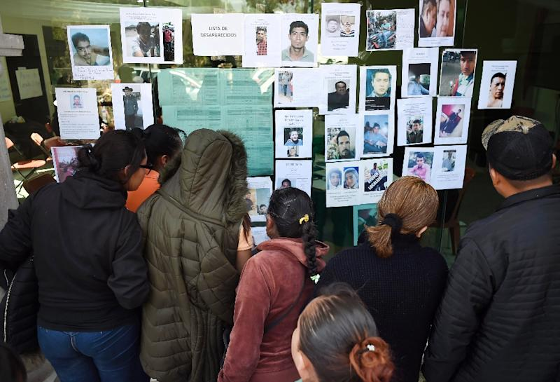 Relatives look for their loved ones among a list of the disappeared after the deadly pipeline blaze in Mexico (AFP Photo/ALFREDO ESTRELLA)