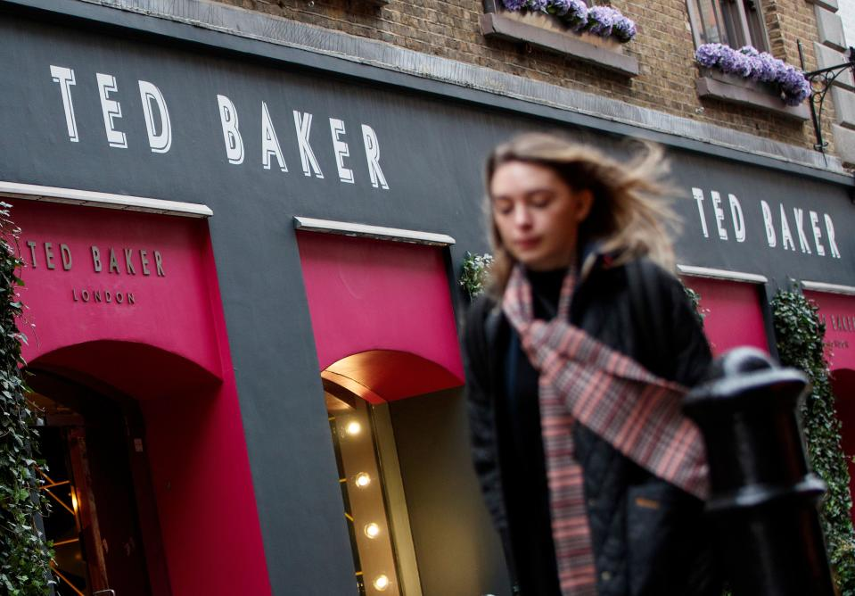 Pedestrians walk past a Ted Baker clothing store in London