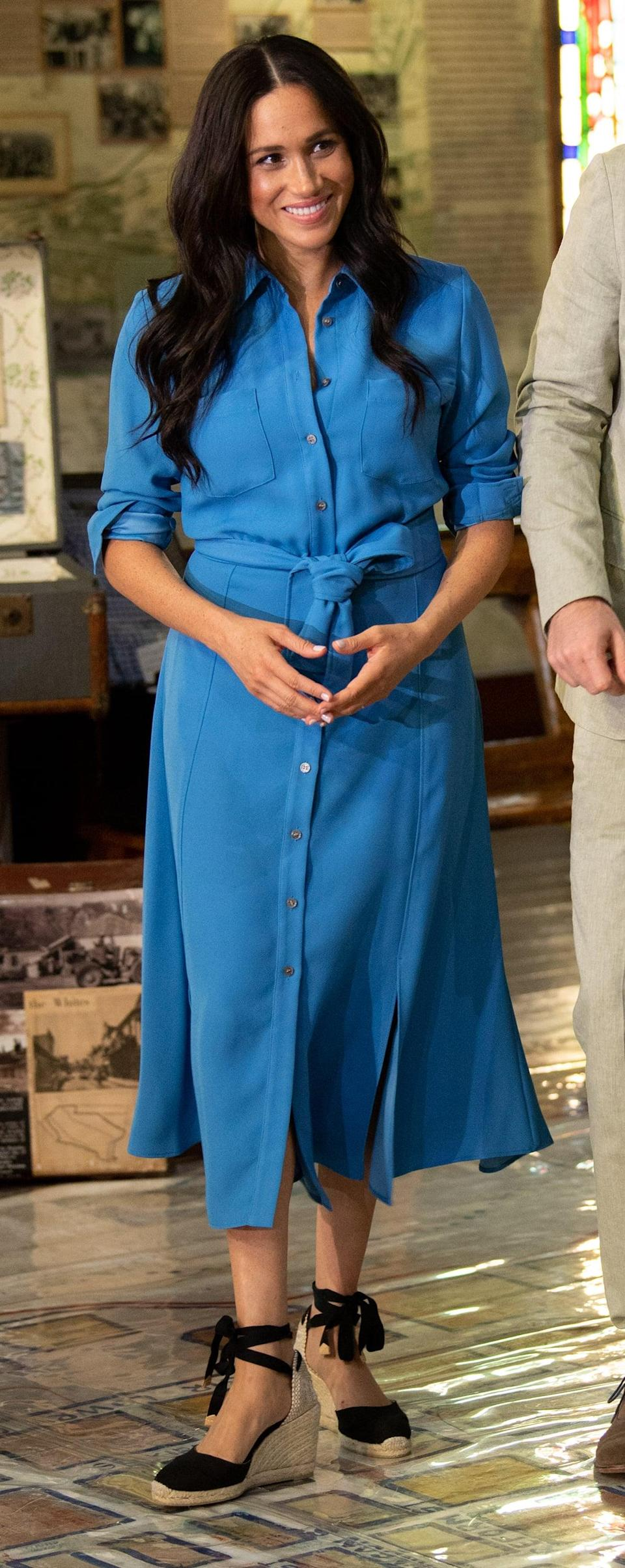 """<p>Meghan wore <a href=""""https://www.popsugar.com/fashion/meghan-markle-wears-blue-dress-again-2019-46665148"""" class=""""link rapid-noclick-resp"""" rel=""""nofollow noopener"""" target=""""_blank"""" data-ylk=""""slk:this sweet shirtdress once again to visit the District 6 Museum"""">this sweet shirtdress once again to visit the District 6 Museum</a> in Cape Town during her royal tour of Southern Africa in September 2019. </p>"""