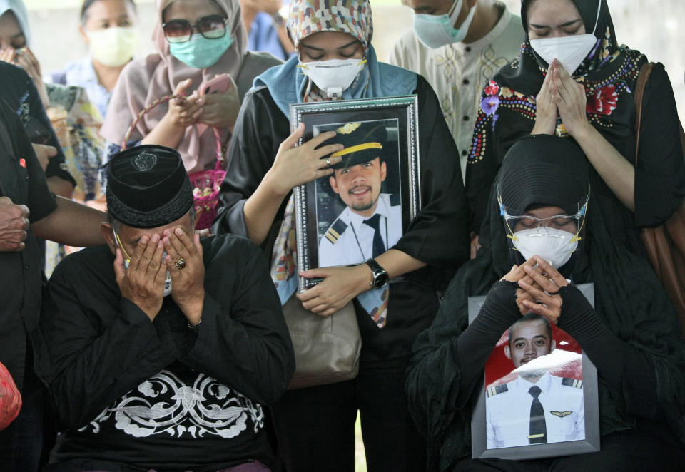 Relatives weep as they pray during the burial of Fadly Satrianto, a victim of the crash of Sriwijaya Air flight SJ-182 in Surabaya, East Java, Indonesia, Friday, Jan. 15, 2021. More searchers and rescuers joined the search Friday for wreckage and victims from the Indonesian plane that crashed in the Java Sea. (AP Photo/Trisnadi)