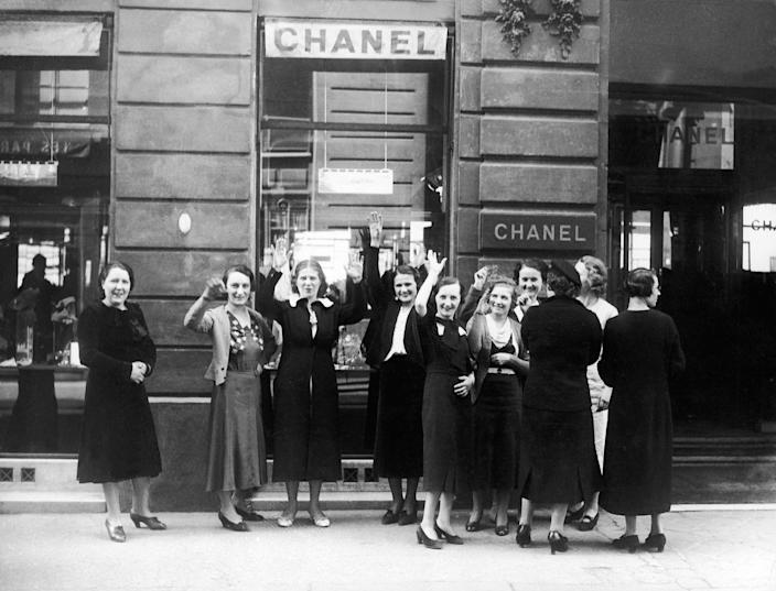 Women stand outside of a Coco Chanel shop in Paris.