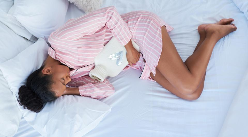 An image of a woman hugging a hot water bottle dealing with cramping