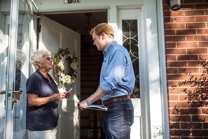 Democrat Chris Hurst, right, canvasses in Blacksburg, Virginia, in July. Hurst unseated Republican Joseph Yost on Tuesday.