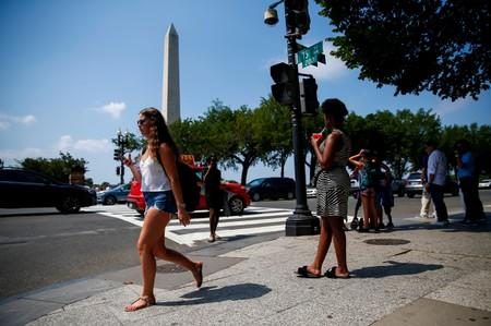 People walk along Constitution Avenue near the Washington Monument during a heat wave in Washington