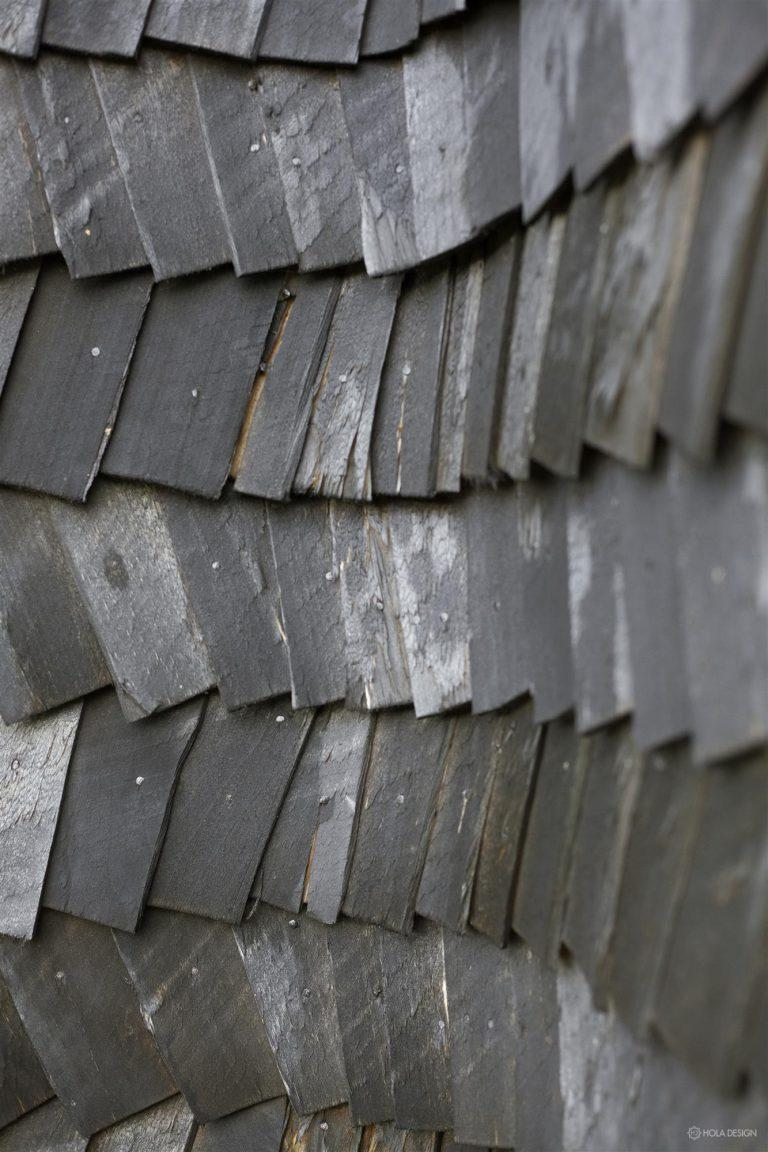 Charcoal-colored shingles give the facade of this HOLA-designed mountain cottage a rather ominous appearance.