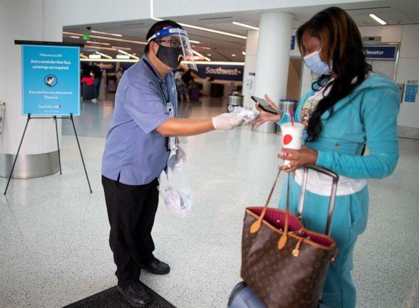 PHOTO: Travel Safely Ambassador Carlos Hernandez hands out a face masks to an airline passenger at LAX airport, as the global outbreak of the coronavirus disease (COVID-19) continues, in Los Angeles, Aug. 4, 2020. (Lucy Nicholson/Reuters)