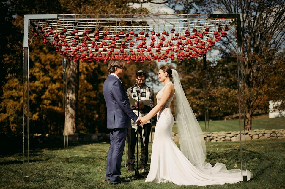 About to say our vows under our Chuppah that was inspired by the Glass House. It was incredible to have the roses swaying above us.