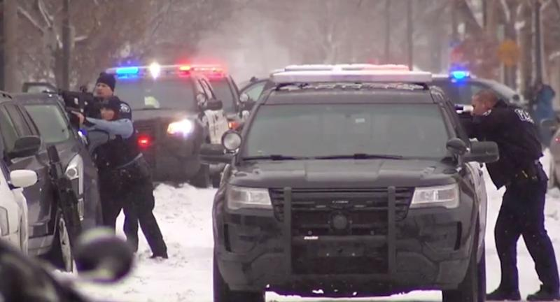 Police with guns stand in the snow preparing to shoot next to their squad cars.