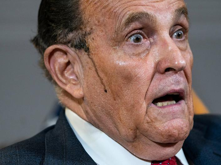 <p>Hair dye runs down Giuliani's cheek during a bizarre appearance at a press conference</p>Getty