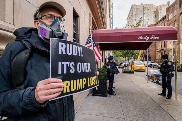 PHOTO: A man holds a sign outside Rudy Giuliani's Upper East Side residence in Manhattan, Nov. 19, 2020. (LightRocket via Getty Images, FILE)