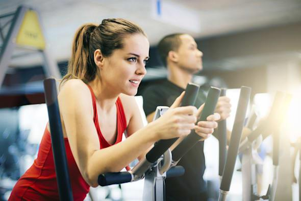 Healthy young woman in GYM using elliptical trainer.