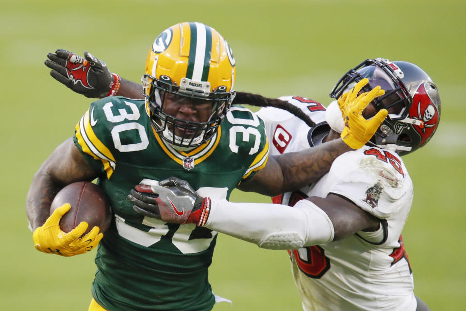 FILE - Green Bay Packers' Jamaal Williams pushes off Tampa Bay Buccaneers' Devin White during the second half of the NFC championship NFL football game in Green Bay, Wis., in this Sunday, Jan. 24, 2021, file photo. A person familiar with the situation says running back Jamaal Williams has agreed to sign with the Detroit Lions The person spoke Wednesday, March 21, 2021, on condition of anonymity because the team had not announced the deal. (AP Photo/Matt Ludtke, File)