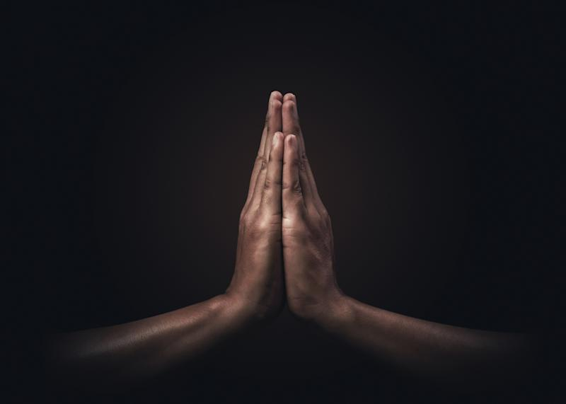 Praying hands with faith in religion and belief in God on dark background. Power of hope or love and devotion. Namaste or Namaskar hands gesture. Prayer position.