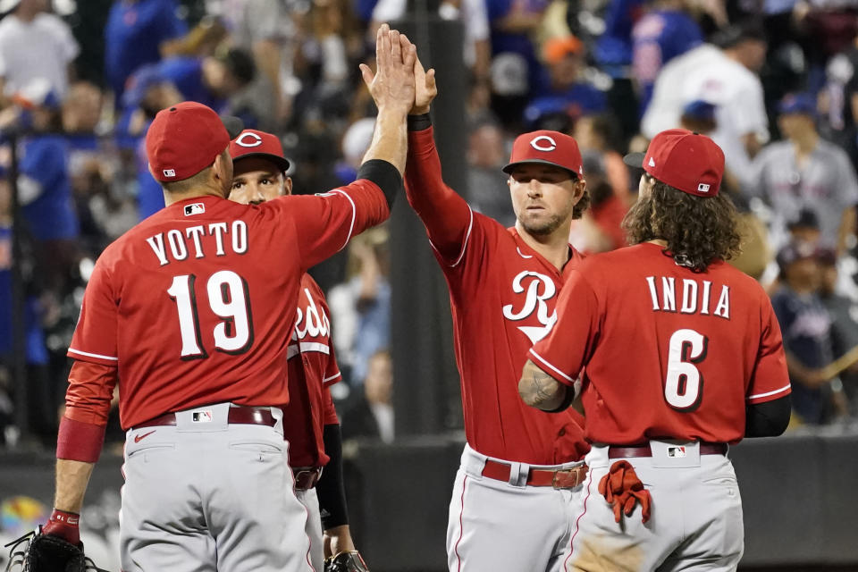 Cincinnati Reds' Joey Votto (19), Eugenio Suarez, second from left, Kyle Farmer, second from right, and Jonathan India (6) celebrate after defeating the New York Mets in a baseball game, Friday, July 30, 2021, in New York. (AP Photo/Mary Altaffer)