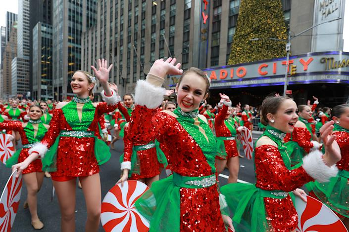Performers dressed as Santas helpers wave to the crowd in the 93rd Macy's Thanksgiving Day Parade in New York. (Photo: Gordon Donovan/Yahoo News)