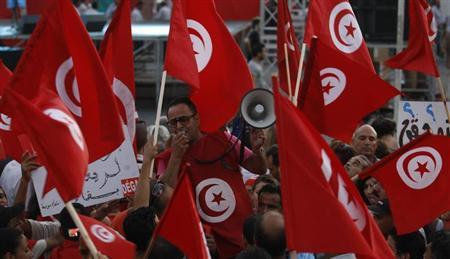 An anti-government protester shouts slogans as others wave flags and signs during a demonstration in Tunis