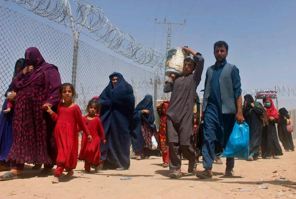 Afghans walk through a security barrier as they enter Pakistan through a common border crossing point in Chaman (AP)