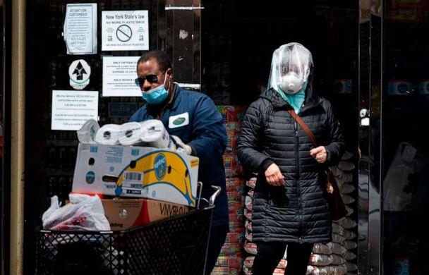 PHOTO: A woman wearing a mask comes out of a  grocery store in the Corona neighborhood of Queens on April 14, 2020, in New York. (Johannes Eisele/AFP via Getty Images)