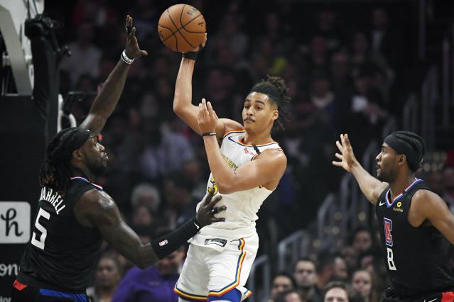 Golden State Warriors guard Jordan Poole, center, passes the ball as Los Angeles Clippers forward Montrezl Harrell, left, and forward Maurice Harkless defend during the first half of an NBA basketball game Friday, Jan. 10, 2020, in Los Angeles. (AP Photo/Mark J. Terrill)