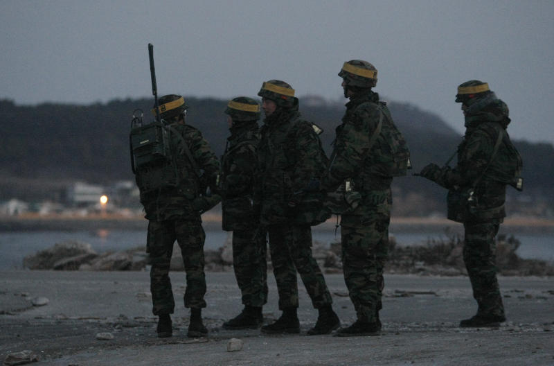 South Korean marines wait their other soldiers to return their base after their patrol along on Yeonpyeong island,  South Korea, Saturday, Dec. 18, 2010.  North Korea warned South Korea on Friday not to stage artillery drills on the front-line island the North bombed last month, saying it would hit back even harder than in the previous attack that killed four South Koreans. South Korea has said it plans one-day, live-fire drills sometime between Saturday and Tuesday on Yeonpyeong.(AP Photo/Ahn Young-joon, Pool)