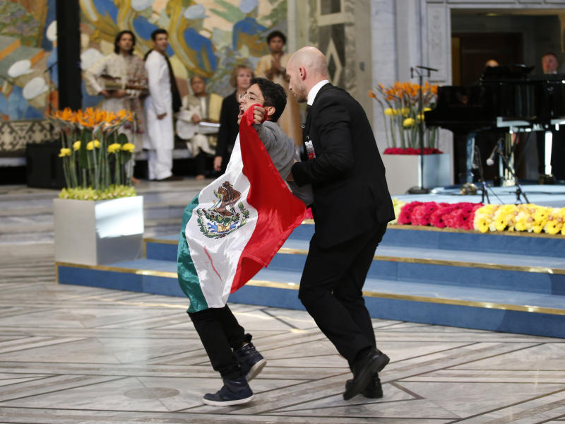 A security officer (right) leads away a man displaying a flag of Mexico during the Nobel Peace Prize awards ceremony at the City Hall in Oslo, Norway, on December 10, 2014 (AFP Photo/Cornelius Poppe)